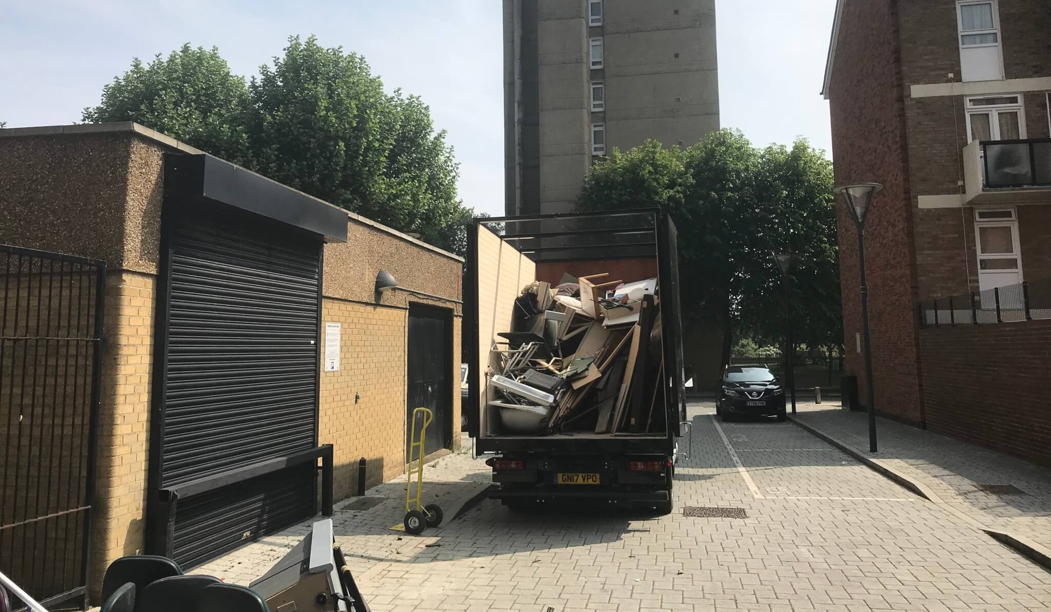 Lorry parked up in street piled full of household rubbish with back open