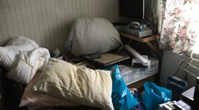 Dirty pillow and various household rubbish piled up in livinging room