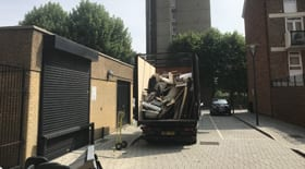 High sided van waiting outside storage area with rubbish piled high in the back